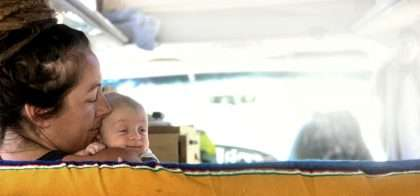 a mother holds her newborn son in the front of a camper van