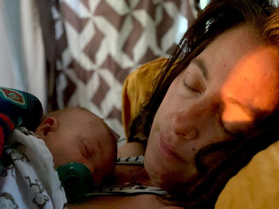 a baby boy sleeps on his mother's chest while camping in a van