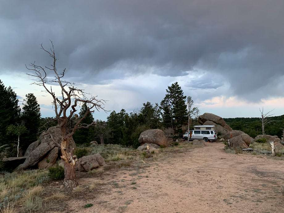 a van camping amongst large boulders