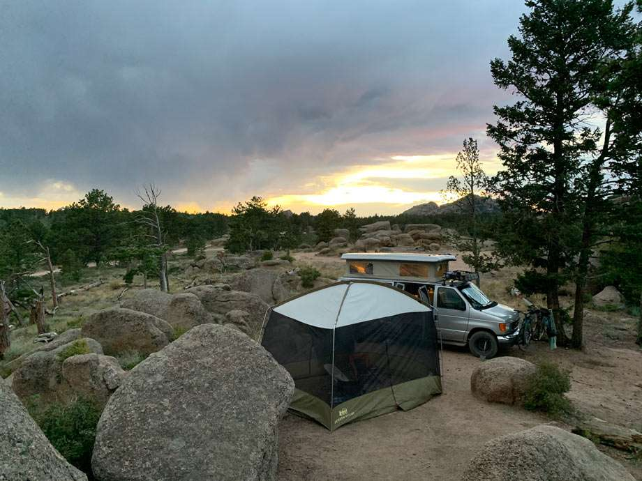 sunset behind a silver van and tent camping at Pole Mountain