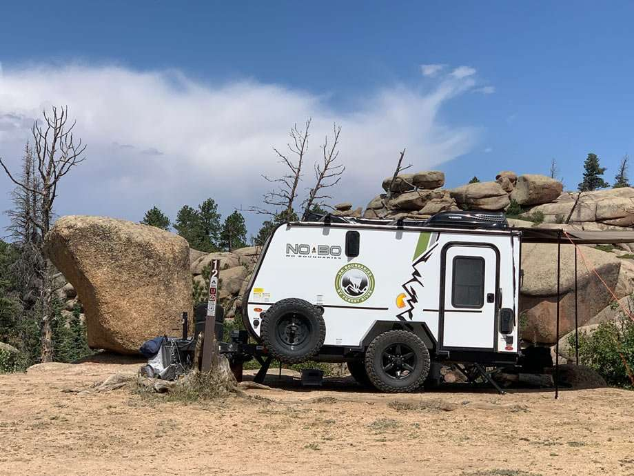 a small, white travel trailer camped amongst boulders