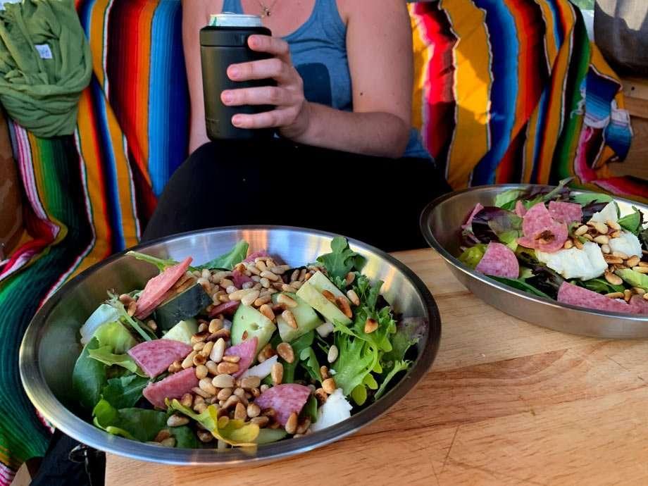 a woman sits behind a salad in a van