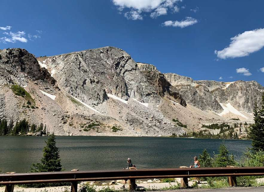 a lake sits between a rocky mountain peak, still laden with snow in August, and the highway