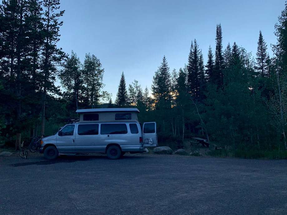 a van camping at a united states forest service campground