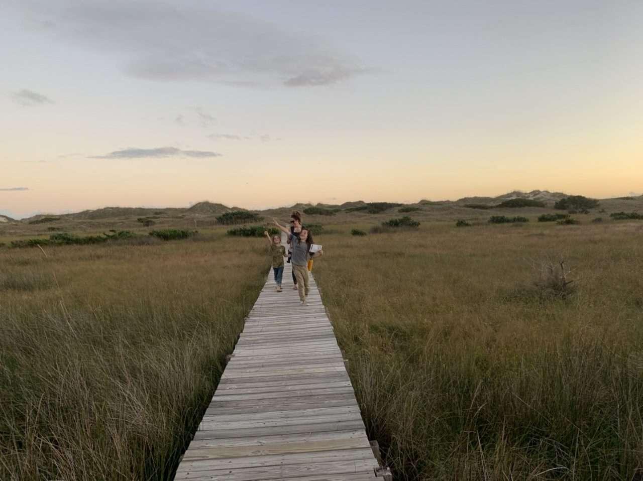A family walks along a boardwalk near the ocean in Cape Hatteras National Seashore