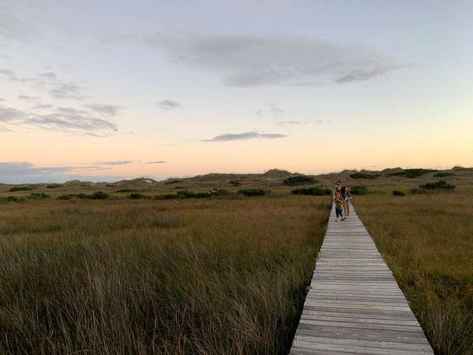 a family walks along a boardwalk through marshlands to from the dunes and beach in Cape Hatteras National Seashore