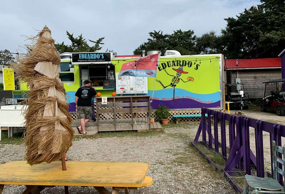 a brightly colored food truck on an island serves hungry customers