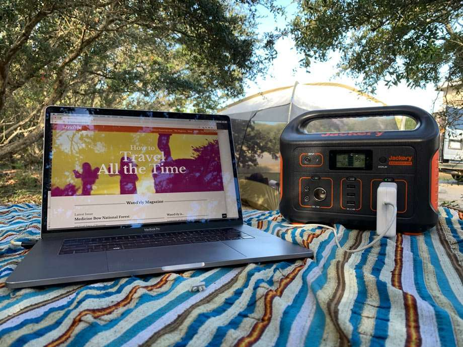 a MacBook Pro laptop plugged into the Jackery at a campground on a picnic table in the shade