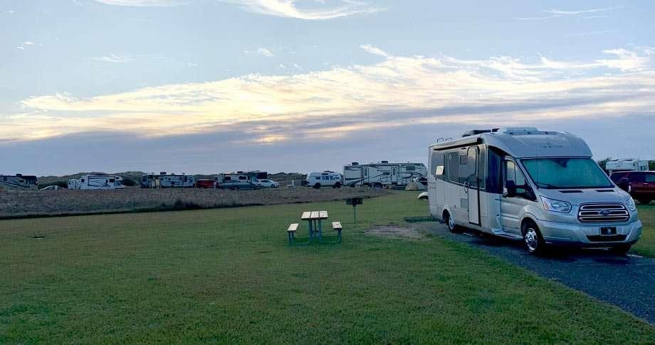 an RV camping in a grassy field near beach dunes