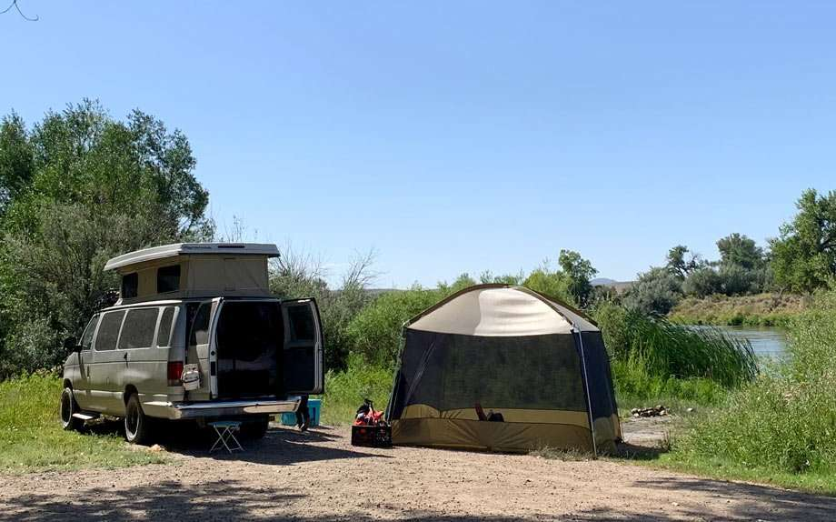 a rather large tent with screened walls set up next to a van camping near a river