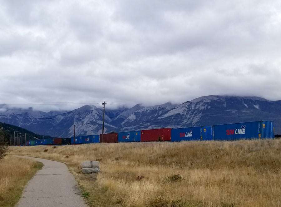 a train slowly rolls through the Rocky Mountains and grasslands of Canada