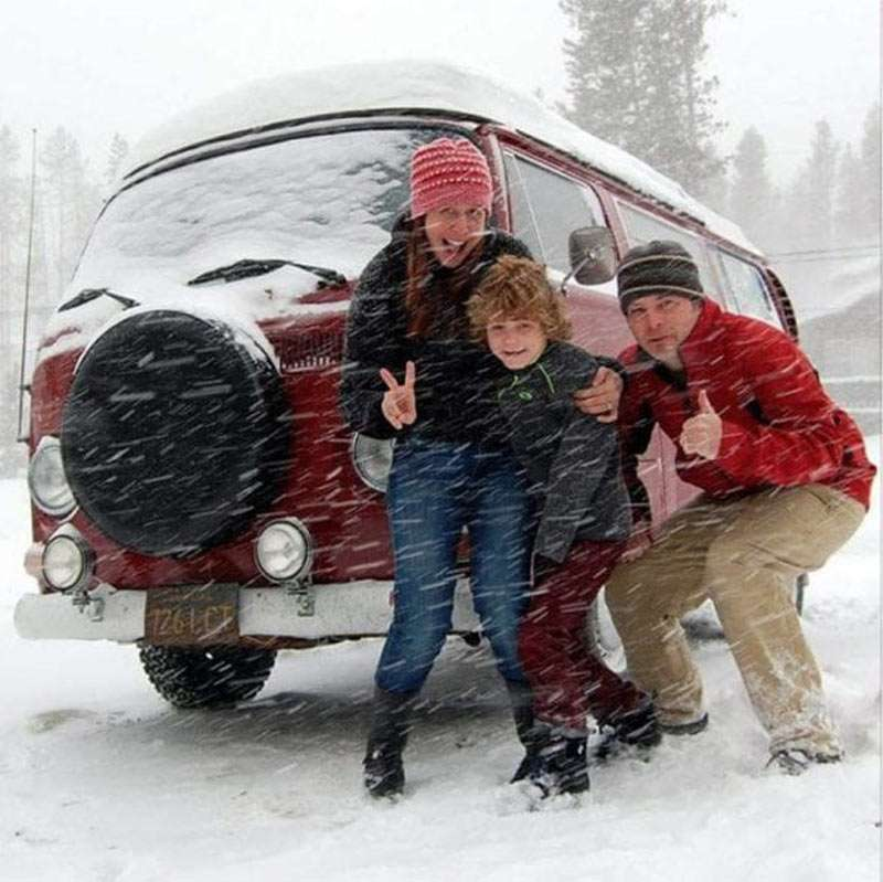 a family gathers in front of a VW Bus in the snow