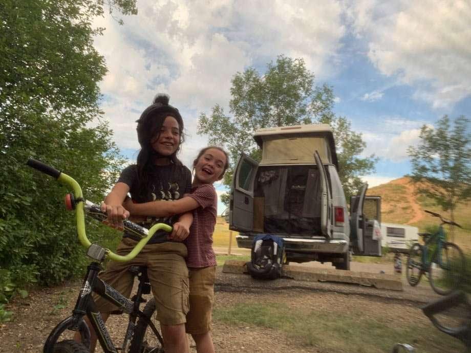 two boys monkey around at a campsite near a van in North Dakota