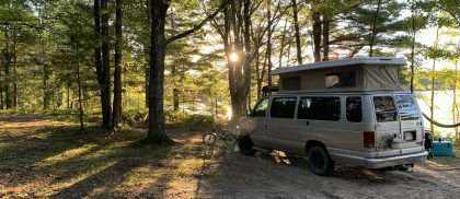 a van camping near a lake in the Northern Woods