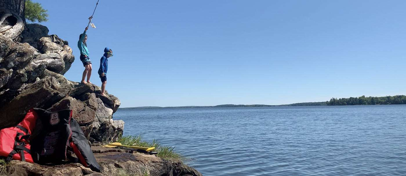 two young boys, a rope swing and infinite summer fun on the lake