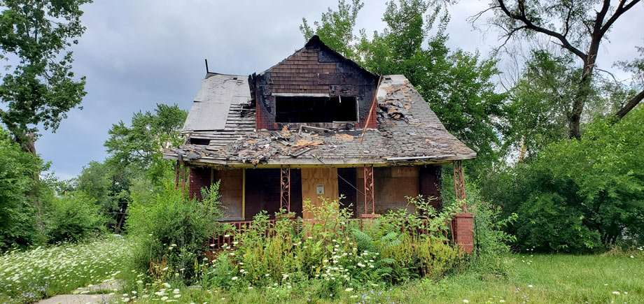 A boarded up and dilapidated home surrounded by overgrown foliage and forest, though a neatly groomed yard
