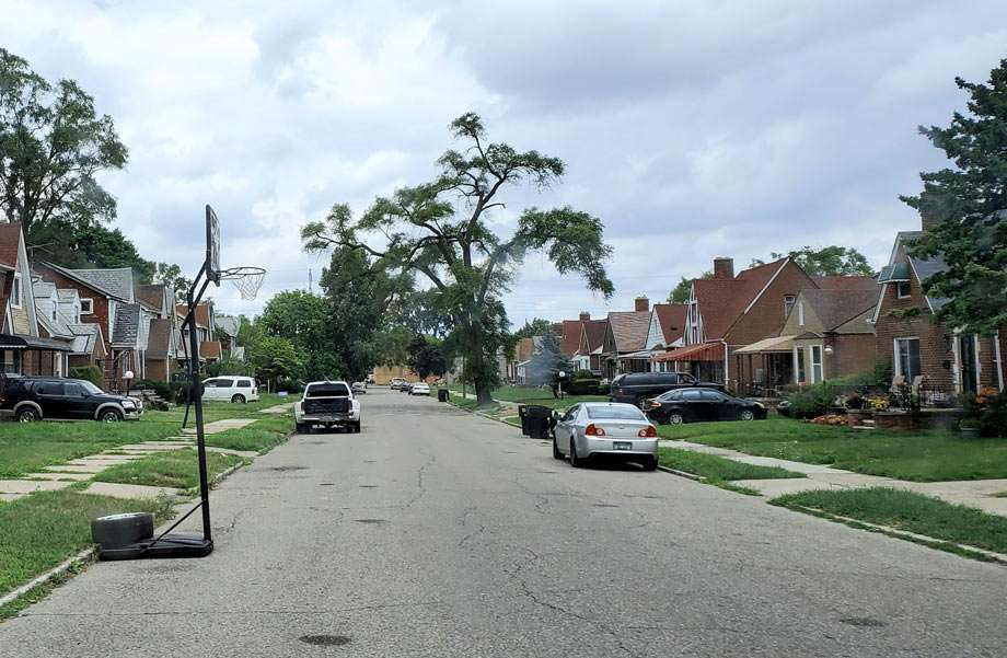 a street with brick homes, trees and a basketball hoop