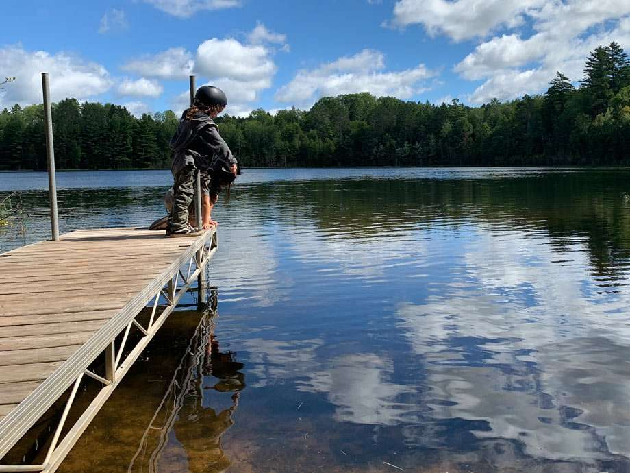 two boys peer off a dock into a small lake