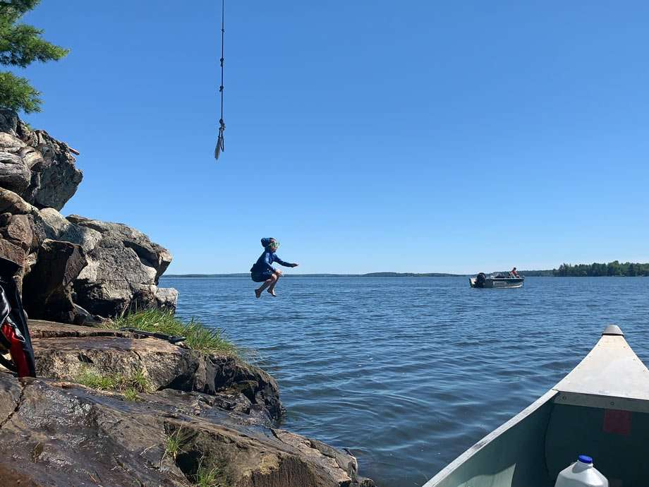 a boy jumps into a lake from a rope swing and off of a small cliff