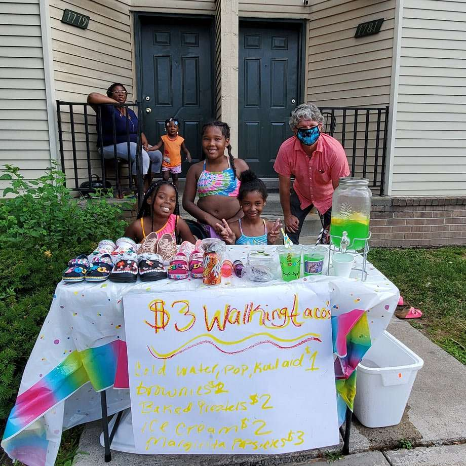 a family of young girls selling various items on a table in front of their home