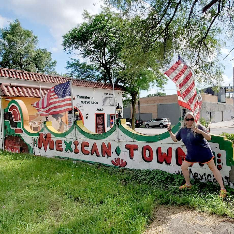 the author poses for a picture in front of a sign that reads Mexicantown