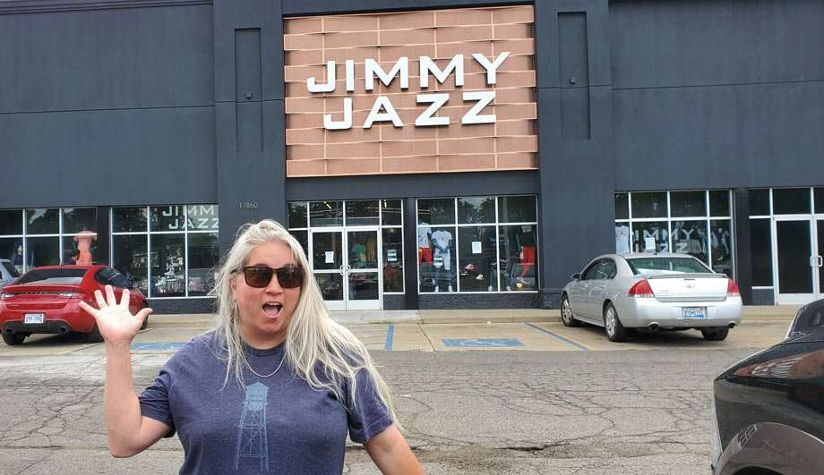 the author waving from a parking lot of a store named Jimmy Jazz