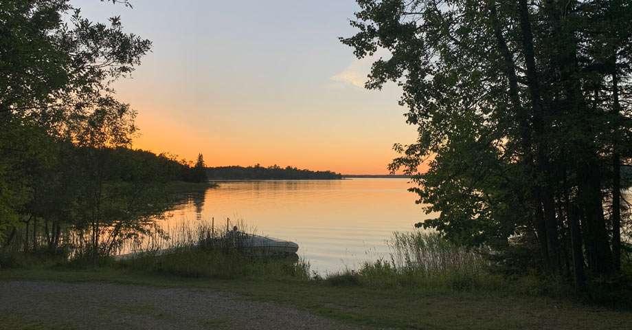 a blazing orange sunset bleeds into Lake Kabetogama