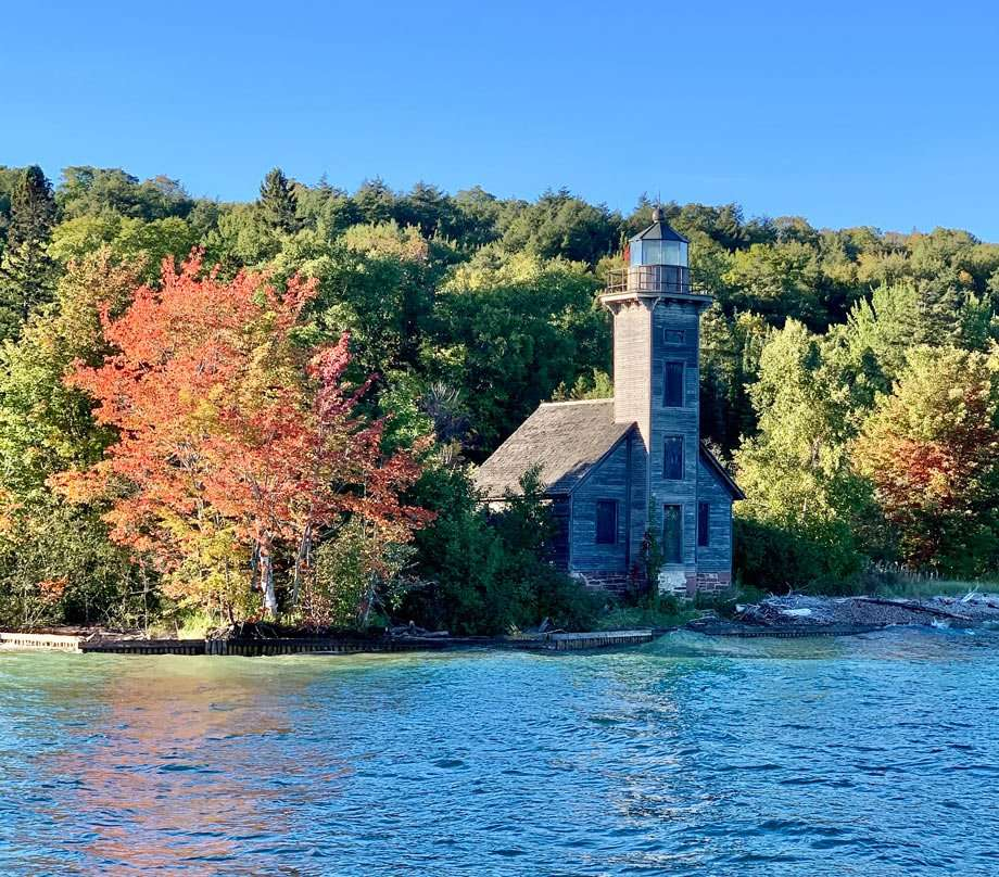 a lighthouse against the autumn leaves of pictured rocks national lakeshore