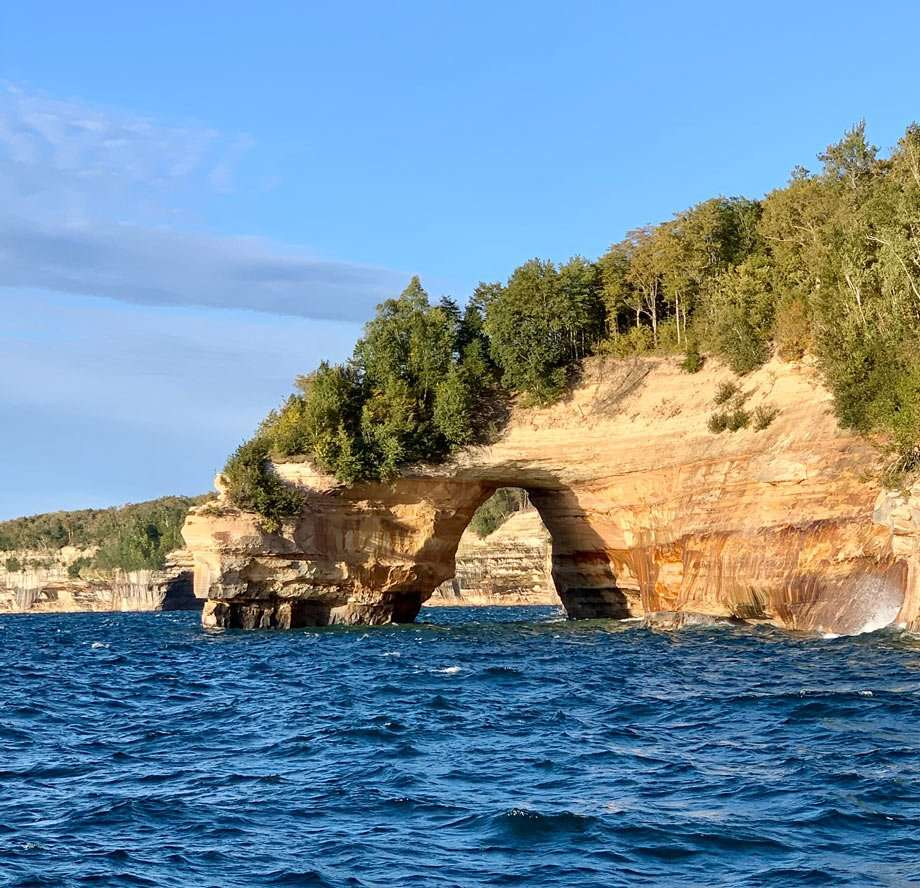 part of the high cliff edge shore of Lake Superior is cut away to form an arch on pictured rocks national lakeshore
