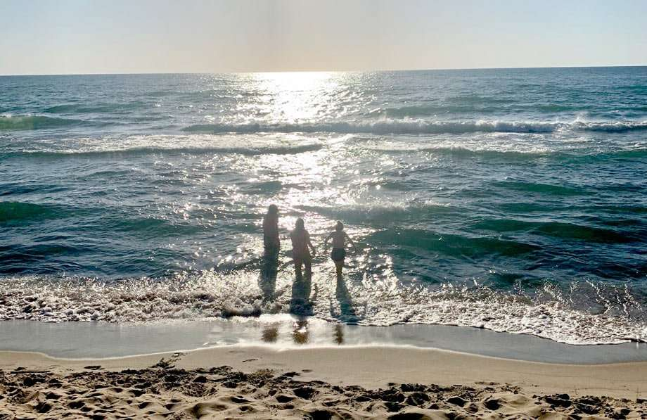 a family testing the waters of lake michigan before a swim
