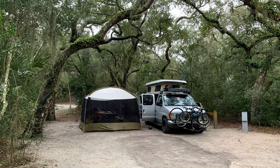 a van and a tent camping in a live oak grove