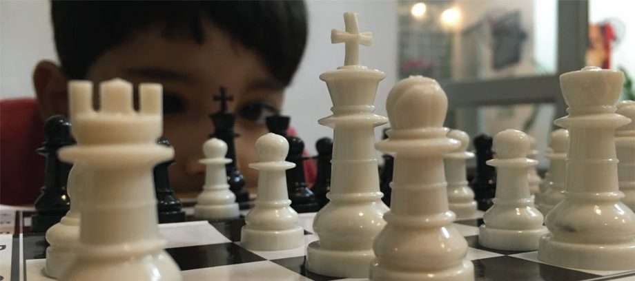 a boy eyes a chess match