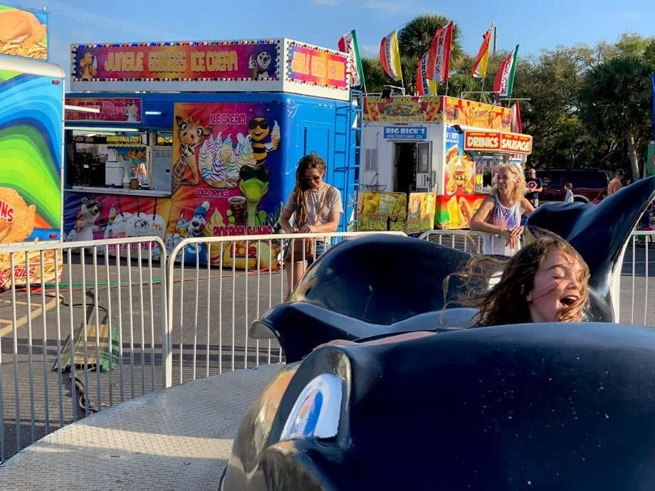 a child enjoys a ride at a carnival while two women laugh