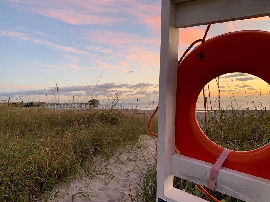 a life preserver, purple sunrise and the cocoa beach pier