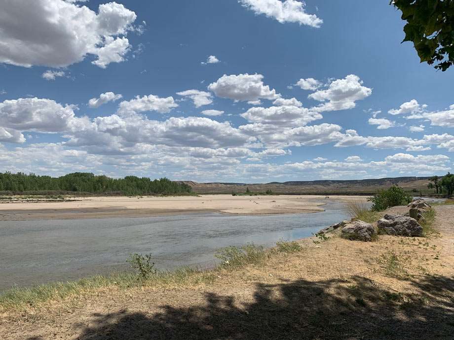 a wide river flows between sandy banks
