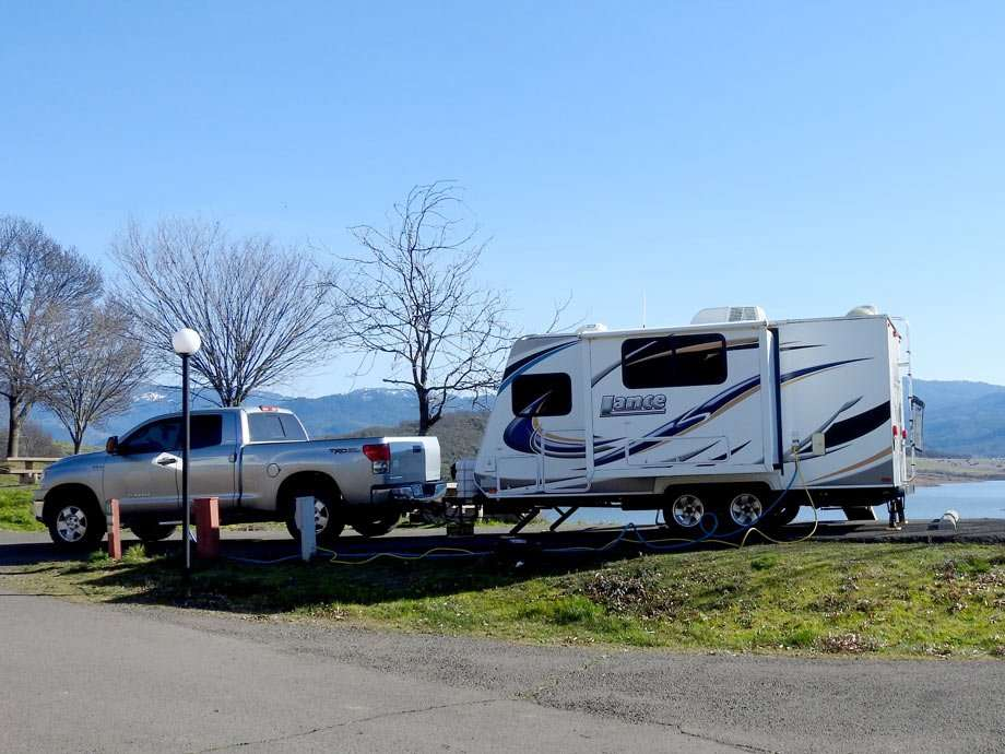 a truck hooked up to a travel trailer, parked at a workamping spot near a lake