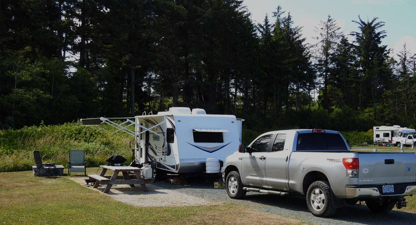 a truck and a trailer parked at a campground, in a site for workampers