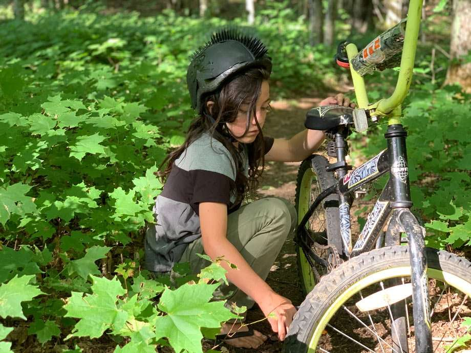 a young boy works on a bicycle on a trail