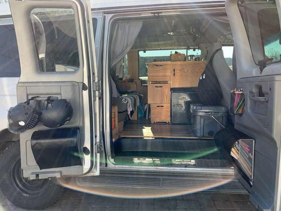 a van with pencils, scissors and workbooks on shelves built onto the side door