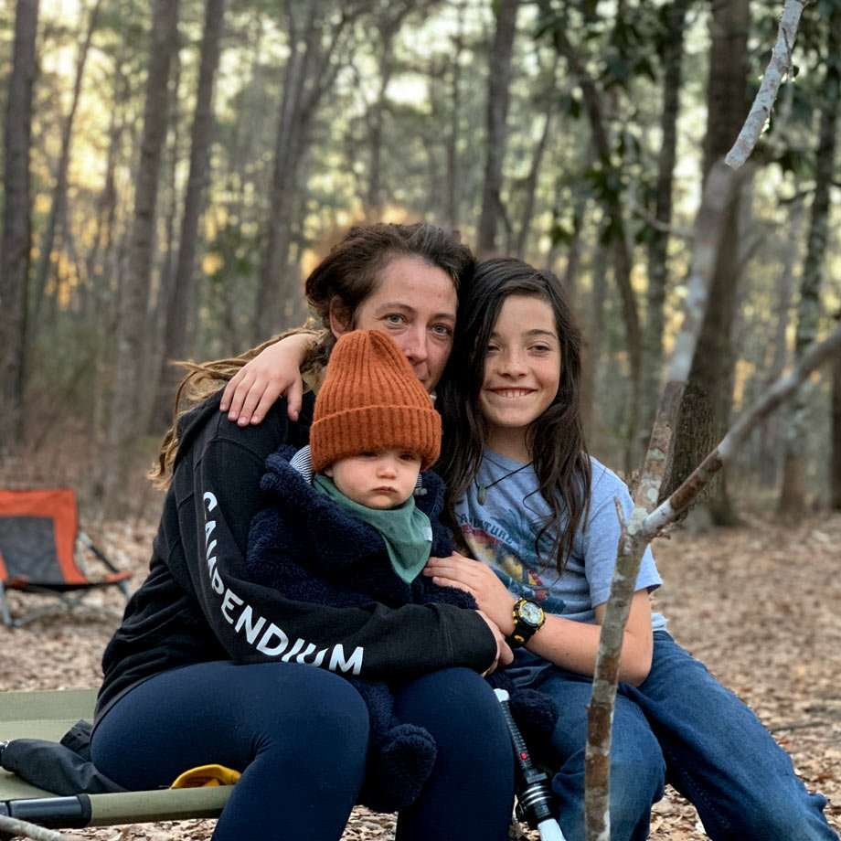 a mother and her ten year old and baby sit near a campfire in the Tuskegee National Forest