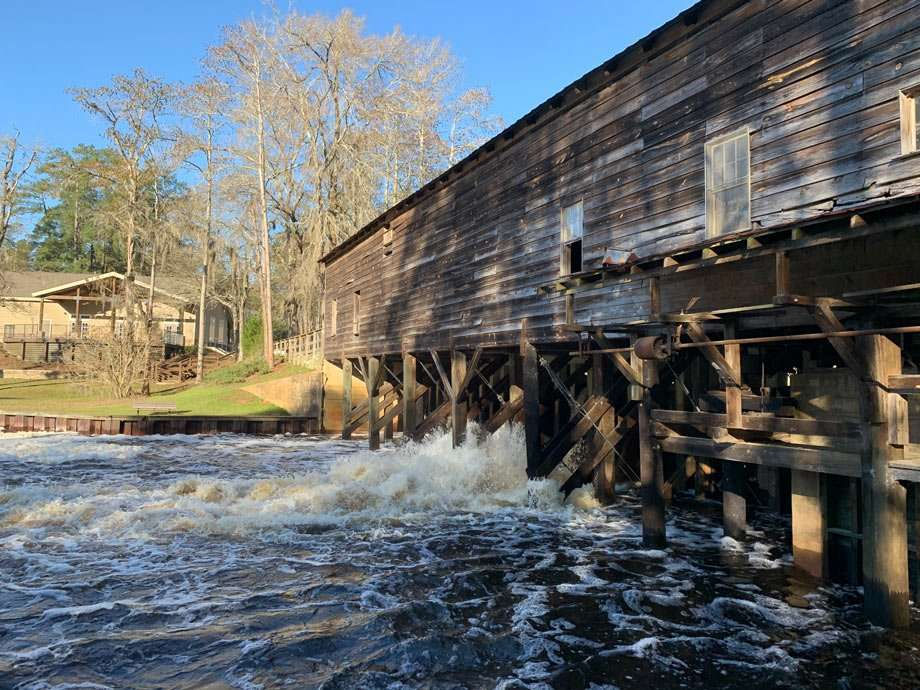 an old mill and dam spills into the river below at George L. Smith State Park in Georgia