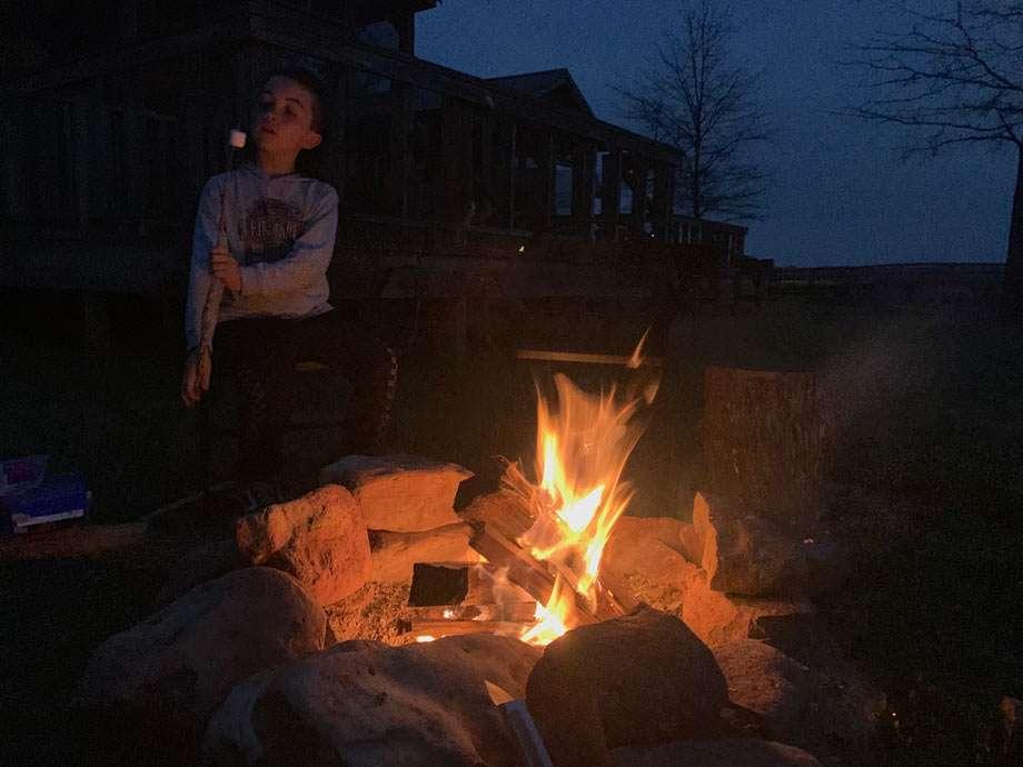 a boy blows on a s'more near a fire