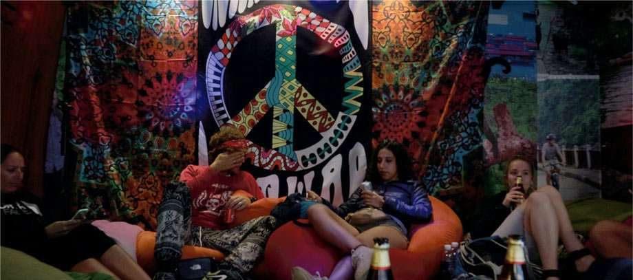 several young people drinking beer on bean bags with a peace sign tapestry hanging in the background in Vietnam