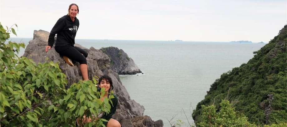 two hikers pose for a photo on a rocky ledge high above the ocean on cat ba island, vietnam