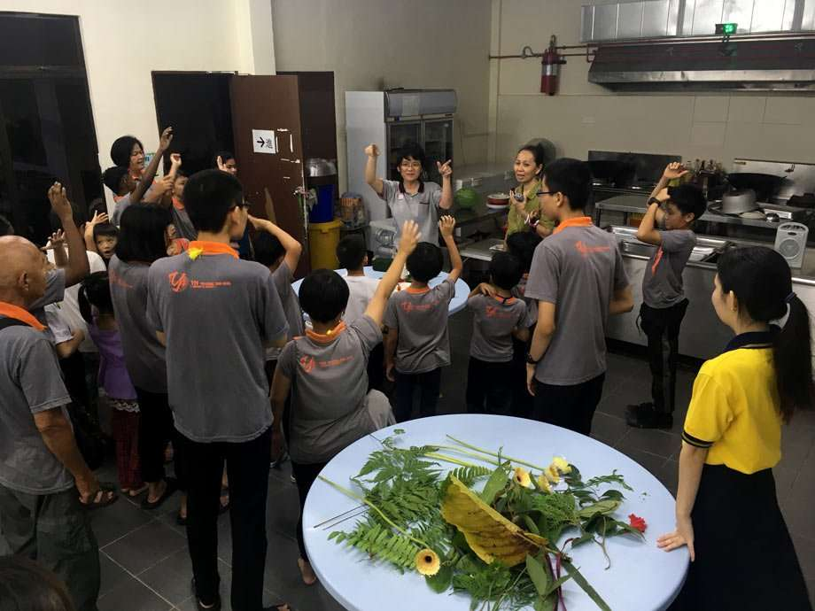 women prepare food in a kitchen for many hungry children