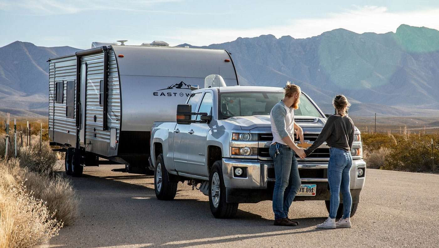 a millenial couple holds hands in front of their truck and travel trailer