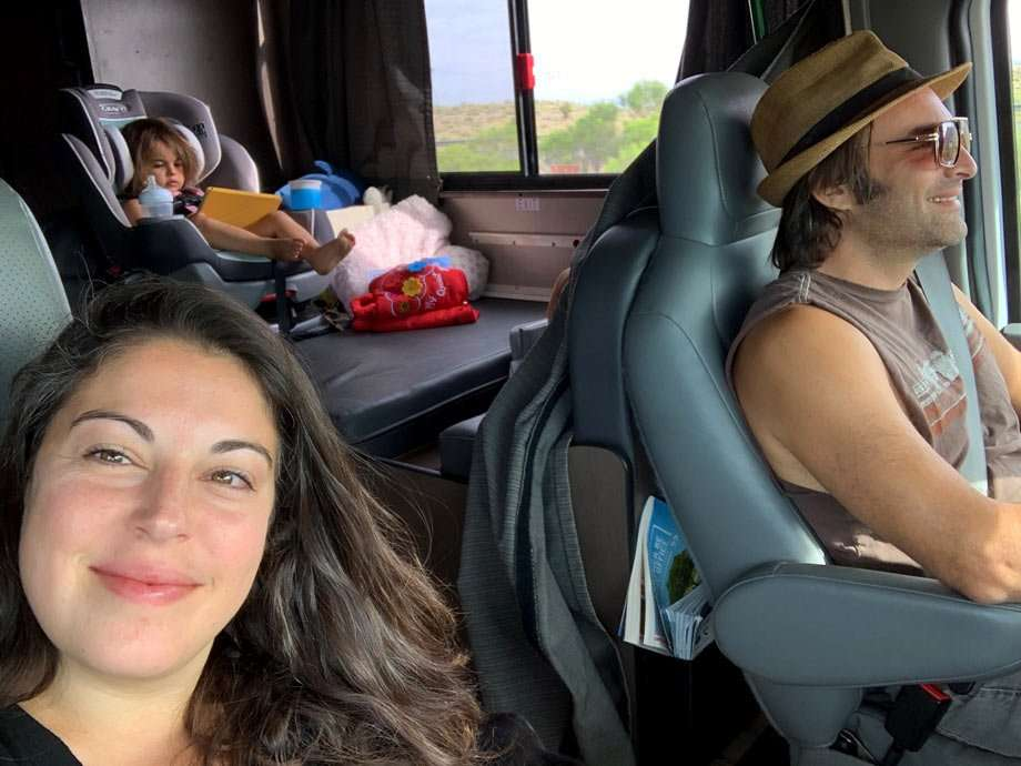 a young girl in a carseat in an RV playing on a tablet while her smiling mom and dad drive on down the road