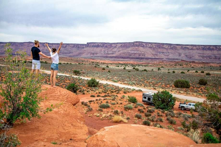 a couple stands on a desert cliff above their campsite along a dirt road in the desert