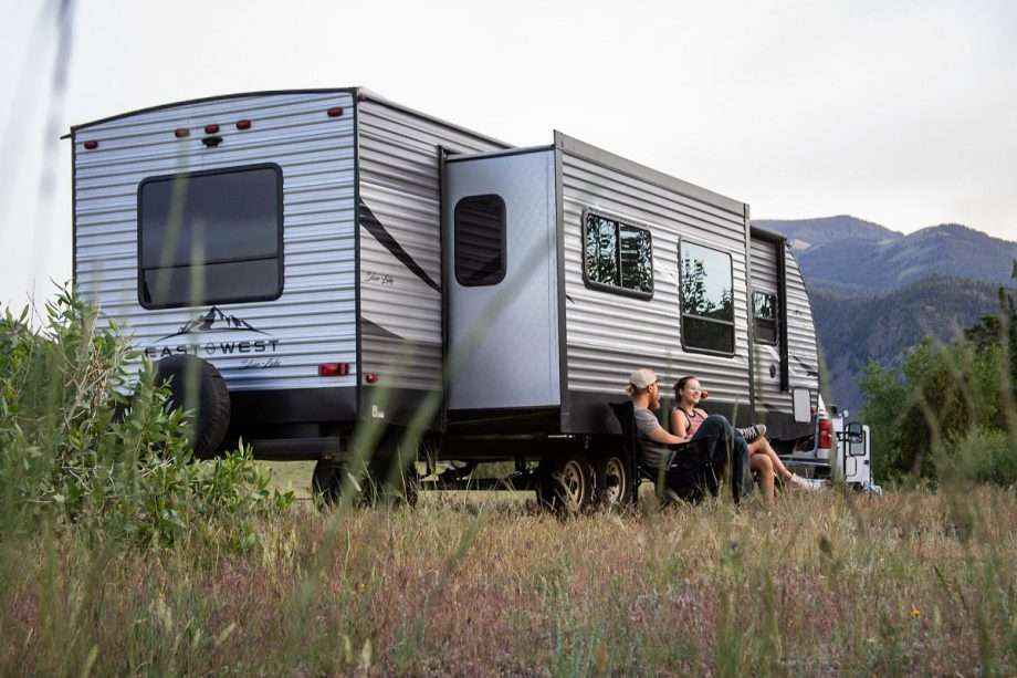 a young couple sits in camping chairs in front of their travel trailer