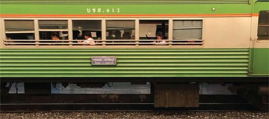 a green and orange train with passengers